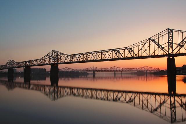 Daybreak at the Wharf: Bridges and water illuminated in warm sunlight.