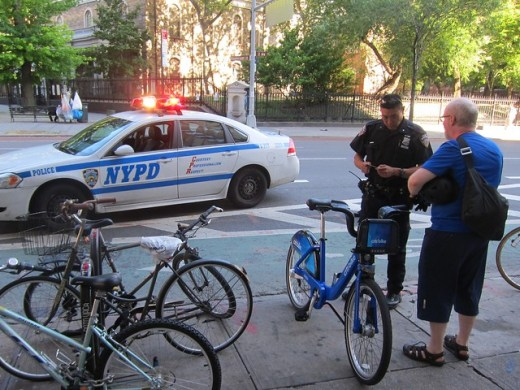 Two NYPD officers, lights flashing, siren whooping, pull over Citi Biker for salmoning on Second Avenue