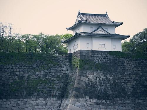수많은 돌로 이루어진 벽 위에 있는, 옛날 일본의 건물.