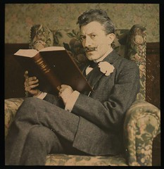 Man with book sitting in chair