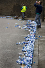 A street strewn with empty water bottles. Two men are sweeping them up while another drinks in the foreground.