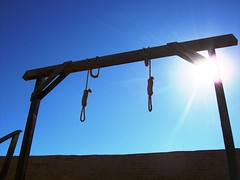 Two hangman's nooses and gallows behind the co...