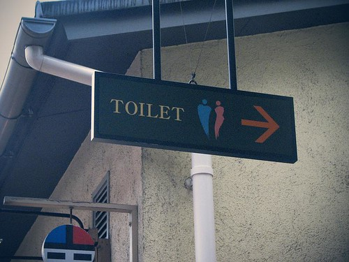Toilet이라고 적힌 작은 판이 천장에 매달려 있다.