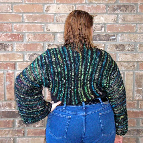 Photo of back view of long-sleeved shrug, knit in garter stitch with novelty thick-thin yarn (Feza Iplik Fiona, in black, yellow, green, blue, and purple).  Improvised pattern.