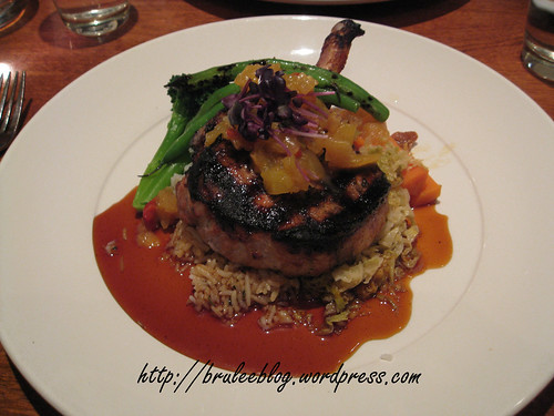 Marinated pork rack chop with Moroccan BBQ sauce, tropical fruit chutney, savoy cabbage and herbed rice