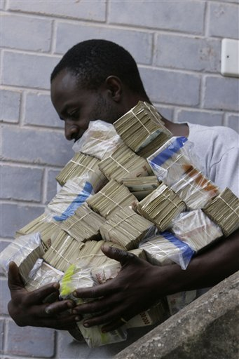 An unidentified man carries some cash for groceries in Harare, Zimbabwe Wednesday, March, 5, 2008. The Zimbabwean currency tumbled to a record 25 million dollars for a single US dollar Wednesday as Zimbabwe battles with the worlds highest inflation currently pegged at over 100 000 percent. (AP Photo/Tsvangirayi Mukwazhi)