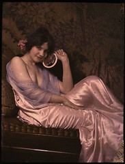 Woman in satin dress holding mirror