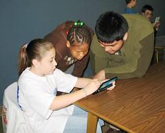 Kelsey demonstrates Nintendog for Ciera & Ivan from the ESC School