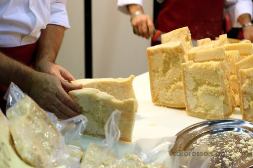 Wedging pieces of Parmigiano Reggiano at Salone del Gusto in Turin