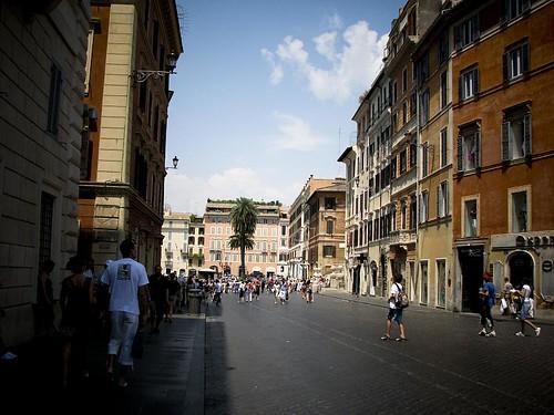 로마의 거리 사진. 건물들이 줄지어 서있다. 길 끝에는 야자수가 보인다.