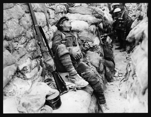 Soldier's comrades watching him as he sleeps, Thievpal, France, during World War I by National Library of Scotland