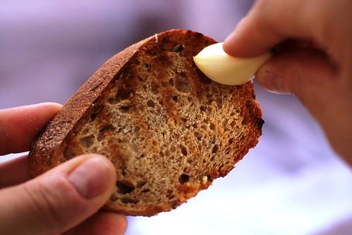 Rubbing garlic on toast slices