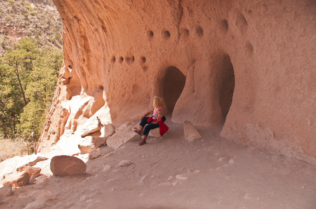 Chris rests after reaching the Alcove House, with rafter holes in the wall behind her