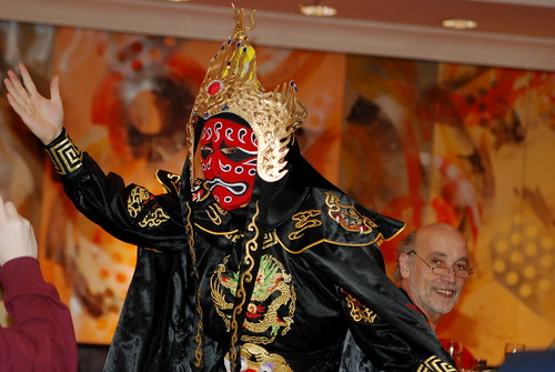 man dancing in traditional Chinese dress while wearing a mask.