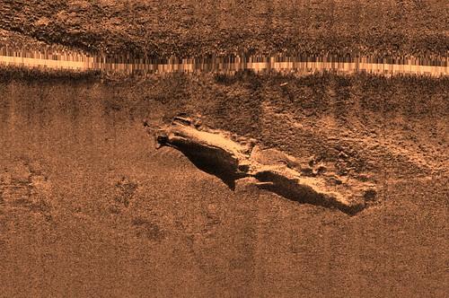 Imagen obtenida con un sonar de barrido lateral de un pecio no identificado. La linea horizontal que se observa en la imagen es el resultado de las señales que emite el sonar verticalmente y señalan la ruta del vehículo. Wessex Archaeology