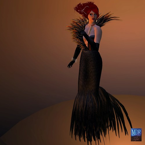 A riot of feathers - black and the firery reds and golds - flame at the foot of the gown.