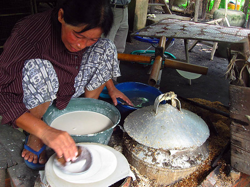 Woman making rice paper crepes