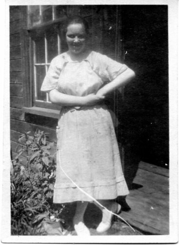 Woman standing in front of house, wearing white dress and shoes.