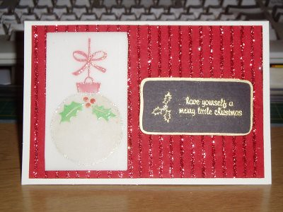 this card was made using parchment paper, i used a stamp and gold/red ink to stamp the bauble in on the reverse, then the holly stamp with green/red ink and clear embossing powder on the front and freestyle embossing ink and clear glittery powder around the outside. Its missing something and im not sure it really works. either way, i wont be doing this technique again.