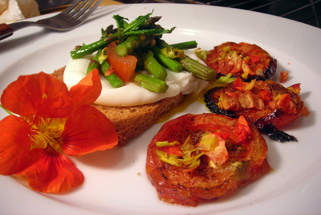 Poached farm egg over toast, with roasted asparagus and tomato salad and quick tomato confit