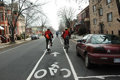 Two bicyclists ride in a bike lane