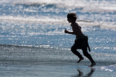 A kid running on a beach