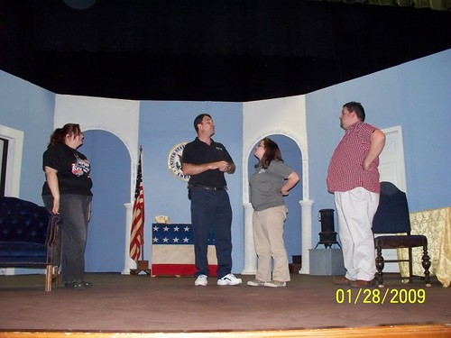 Father Drobney (Westley Annis) shows off his magic tricks for Marion, Susan (Clara Arceneaux) and Walter Hollander.