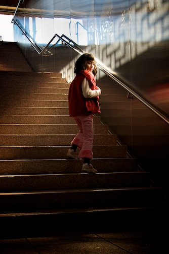 A girl walks up steps at the subway exit for Lungshan Temple, Taipei, Taiwan.
