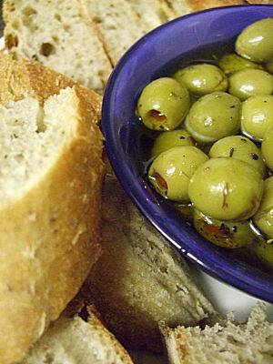 crusty ciabatta, still warm from the oven, served with green olives, stuffed with piemento, in garlic and herb infused olive oil