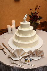 The beautiful white wedding cake with smurfs all around.
