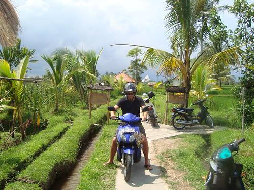 Tim rides motorcycle to the Sari Organik restaurant