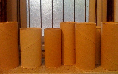 empty toilet rolls under an orange fluorescent  light