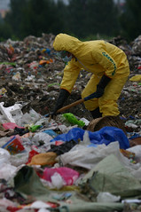 A Greenpeace Water Patrol activist wearing a protective suit shovels trash to take samples from a dumpsite in Taytay.