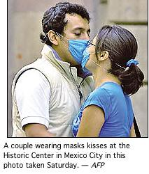 two people kissing while wearing surgical masks