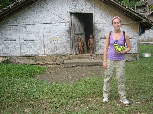 Hannah with bananas and naked little girls peering out of their house