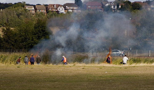 Canvey Island's Railway and Model Engineering Club members tackle a grass fire with long shovels and water.
