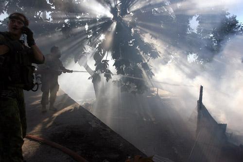 Tentara Australia berusaha memadamkan api yang membakar rumah-rumah warga di Komoro, Dili Timor Leste. Setelah dua minggu kerusuhan yang terjadi akibat krisis politik warga masih terus membakari rumah-rumah yang diangggap milik musuh mereka.