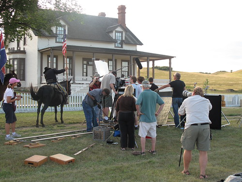 A film crew surrounds the talent on the grounds at Fort Abraham Lincoln.