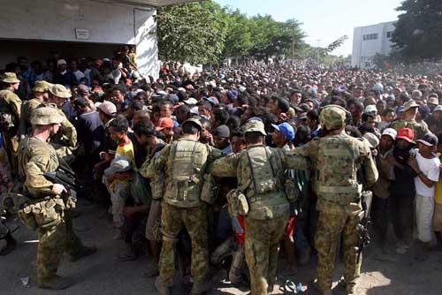 Tentara Australia membuat antrian untuk membagikan beras di gudang pemerintah di Bebora, Dili untuk mencegah penjarahan karena bahan makanan mulai sulit mereka dapatkan sejak kerusuhan yang disebabkan krisis politik di Dili, Timor Leste.