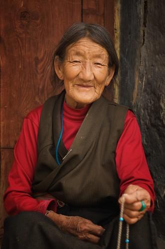 An elderly Tibetan woman sits on her doorstep in Ganze, Tibet (China).