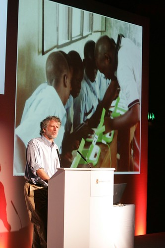 David Cavallo presents infront of an image of five boys with laptops in an African  classroom