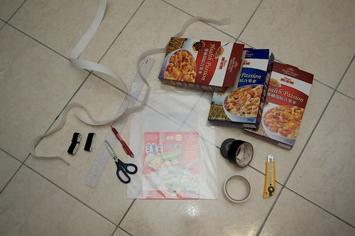 Al the materials youre going to need to make a DIY soft box:  Difusing material (a thin cutting board), cereal boxes, black tape, scissors or a knife, Velcro (sticky on one side), a pencil and a ruler.