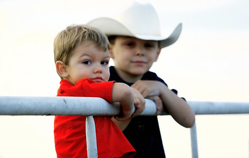 Two youngsters hanging on the arena railing. The one in the cowboy hat nudged the red-shirted one and whispered - audibly - LOOK AT HER. Shes trying to take our picture!