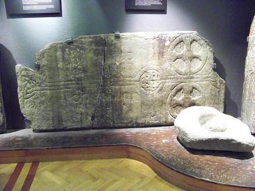 Grave slab and bullaun stone in Glendalough Visitor Centre