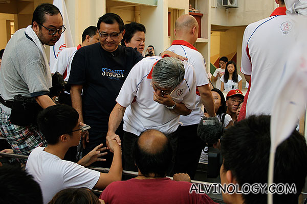 A young boy shaking Mr Chiam's hand