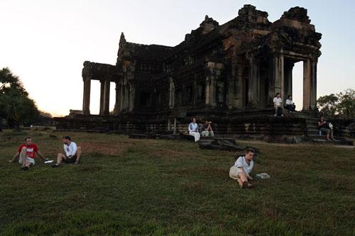 Beberapa orang turis asing bersantai menikmati sunset di areal Angkor Wat di Siem Reap, Kamboja.