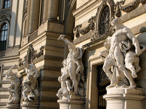 Statues decorating the entrance of Hofburg by you.