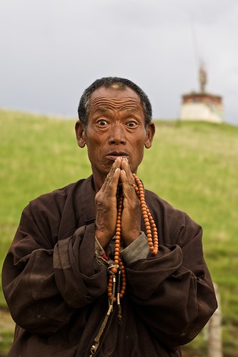 A pilgrim prays below a chörten in Litang, China (Tibet)