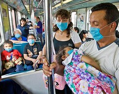 a family wearing surgical masks on the bus