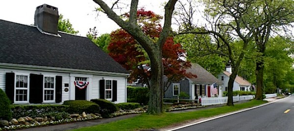 Three small white Cape Cod style homes in Barnstable MA with red, white and blue bunting for the 4th of July.